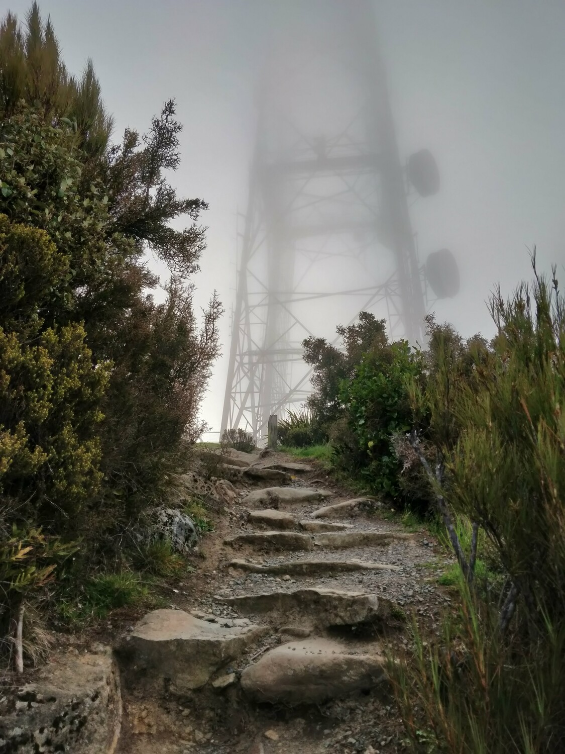 The path leads up a final set of stone steps, with the transmission tower a short distance away. The fog is so thick that the tower fades into mist, its midpoint being almost indistinguishable from the sky.
