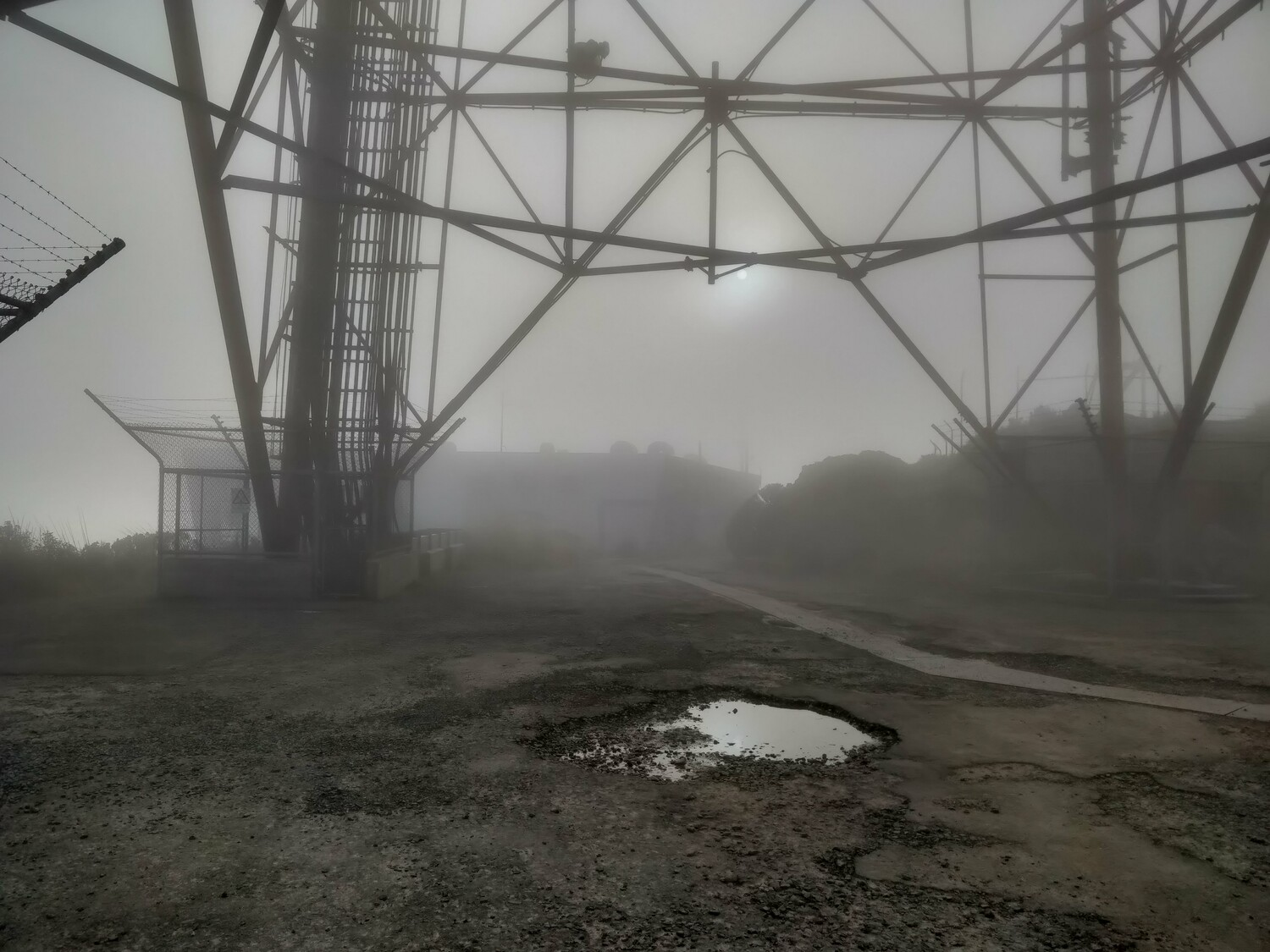 Standing underneath the tower. There is the outline of a grey building visible in the grey mist. The sun weakly shines through, a perfect dim circle that's comfortable to look directly at. The ground is gravel with an unattractive puddle in the middle of it.